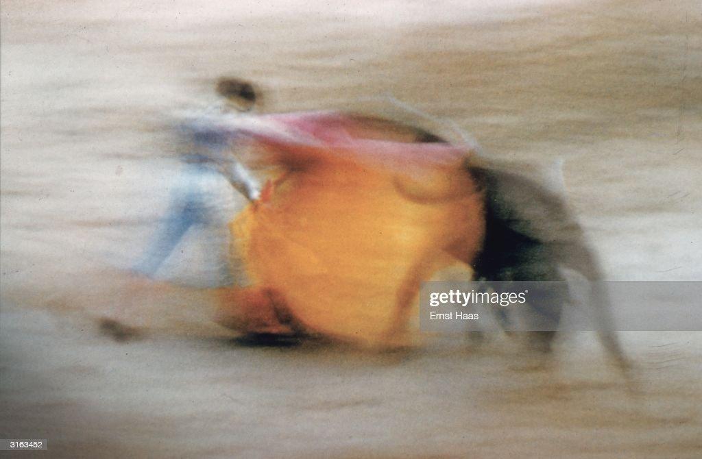A matador waves his cloak at a charging bull.