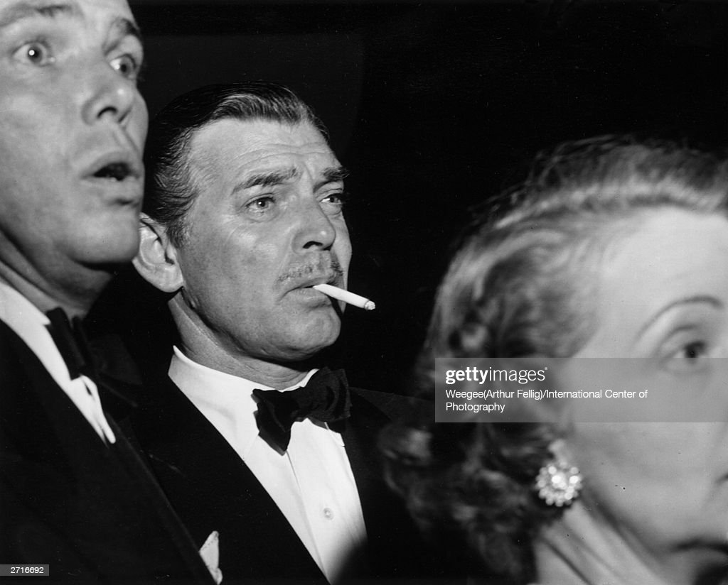 Premium Rates Apply. Clark Gable (1901 - 1960) smokes a cigarette with an astonished friend in Hollywood, California. (Photo by Weegee (Arthur Fellig)/International Center of Photography/Getty Images)