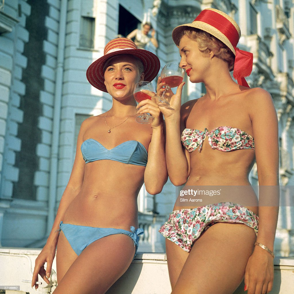 Premium Rates Apply Two bikiniclad holidaymakers enjoy a glass of wine outside the Carlton Hotel Cannes
