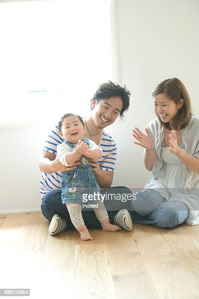 Prents with baby girl (18-23 montsh) on floor