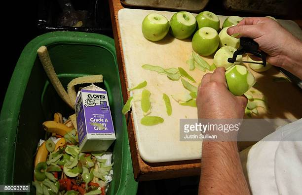 A prep cook at MoMo's restaurant drops apple skins into a food scrap recycling container April 21 2009 in San Francisco California Norcal Waste...