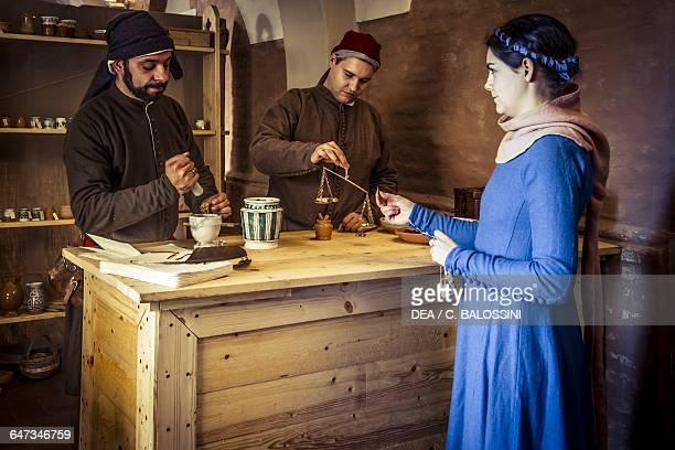 Preparation of a sugarbased medicine in the apothecary run by Diotaiuti di Cecco Imola Italy mid14th century Historical reenactment