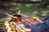 Preparation of barbecue, Grilled skewers on plate outdoor. Grilled shish kebab on metal skewer. Chef hands cooking roasted meat slices barbecue with lots of smoke. BBQ fresh beef chop slices. Traditio
