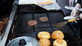 A preparation of burger beef barbecuing on a hot gas stove. (Selected focus)