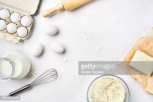 Preparation of the dough. A measurement of the amount of ingredients in the recipe. Ingredients for the dough: flour, eggs, rolling pin, whisk, milk, butter, cream. Top view, space for text : Stock Photo