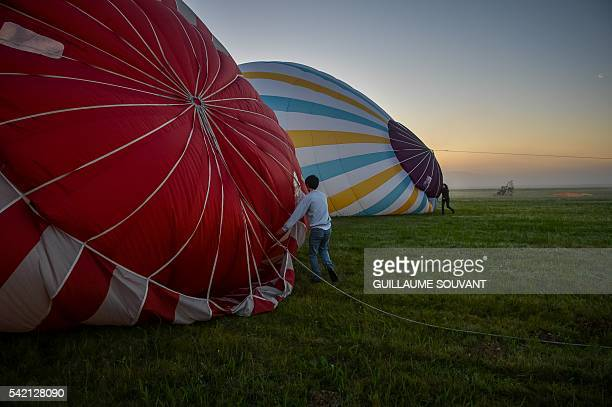 Preparations are made before French trapeze artist Isabelle Ponsot takes off in a hot air ballon to perform while hanging from the balloon above...