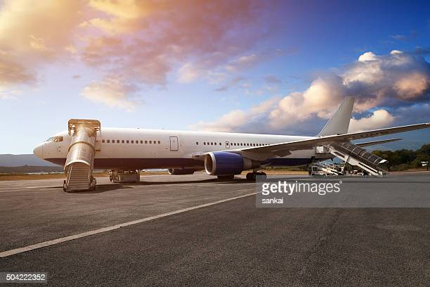 Preparations of passenger jet airplane in airport in the evening