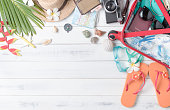 prepare accessories and travel items for summer on white wooden board, flat lay, top view background