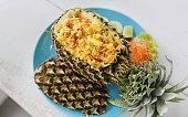 Prepared pineapple fried rice served inside of a pineapple carved like a bowl.