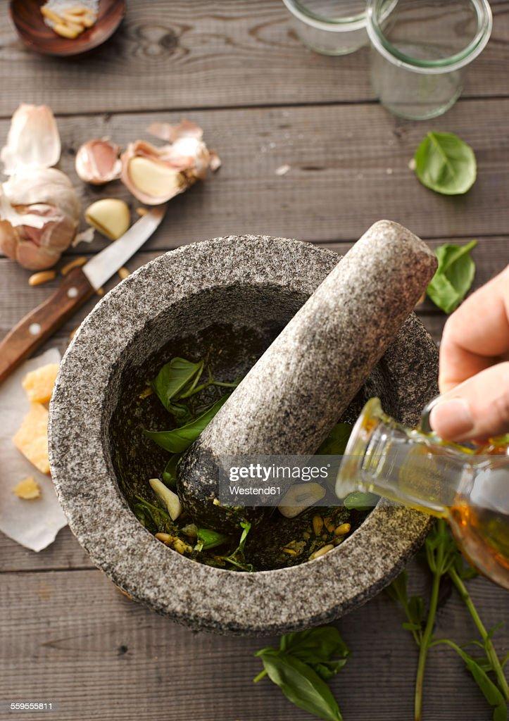 Preparing basil pesto with mortar