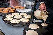Men preparing delicious pancakes on the street food market in Bergen, Norway