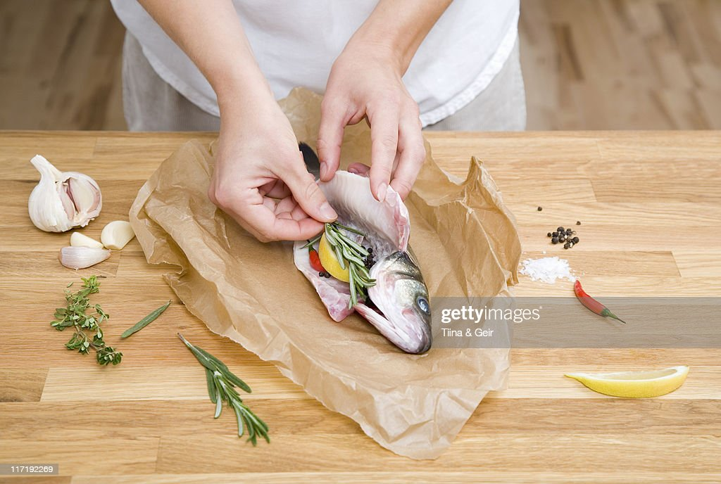 Preparing fish with herbs, spices, lemon : Stock Photo