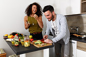 Young couple in kitchen preparing together vegetarian meal.Preparing fruit salad.Evening.