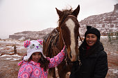 Mother and daughter in winter preparing for a ride in the snow.