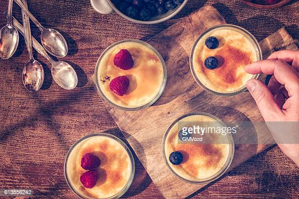 Preparing Homemade Creme Brulee with Berries