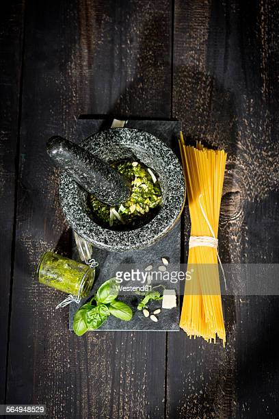 Preparing pesto alla genovese with mortar, uncooked spaghetti