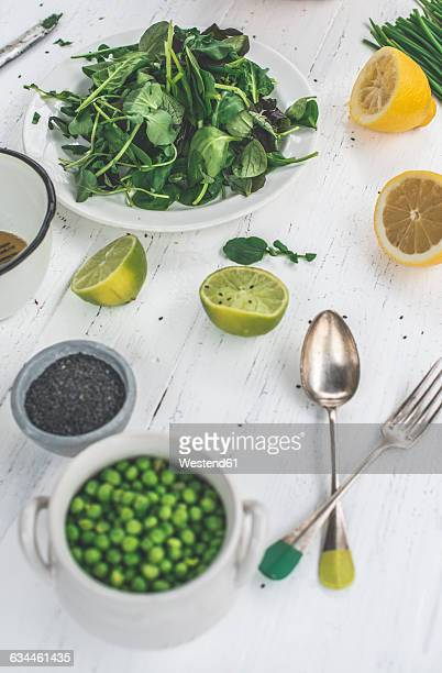 Preparing salad of peas, baby spinach, watercress, chives and black sesame with dressing of lime and sesame oil