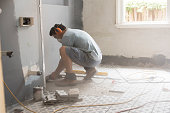 Grinding the bathroom floor in preparation for tiling during a home renovation in Sydney Australia