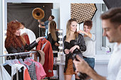 Young dresser preparing clothes for young pretty model