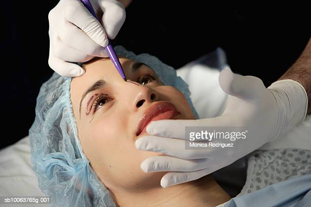 Preparing woman in surgical gown for face lift
