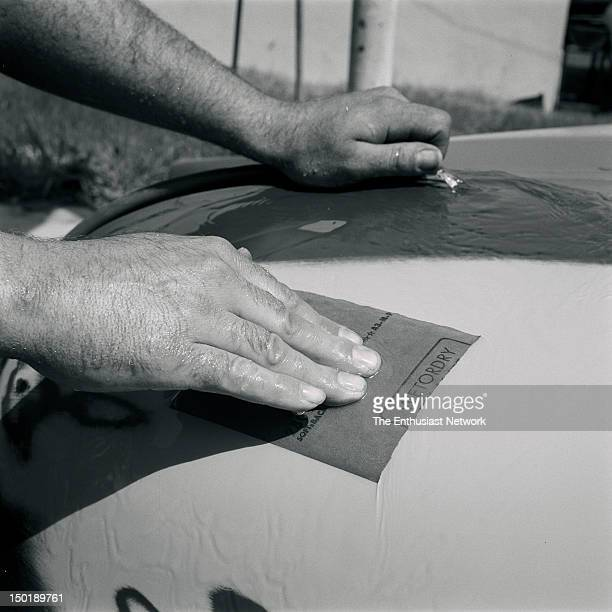 Prepping And Painting A Custom Car Old Chevrolet custom gets wetsanded before another coat of primer is applied Man holding water hose and sheet of...