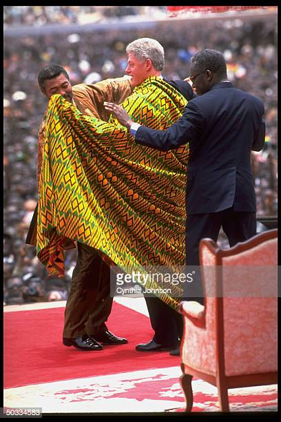 US Pres Bill Clinton being wrapped in kente cloth during appearance in Independance Square on stop at start of his African tour