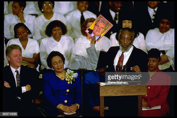 Pres Bill Clinton laughing as comedian Dick Gregory brandishes copy of TIME Man of Year Newt Gingrich issue sitting with Coretta Scott King Rev...