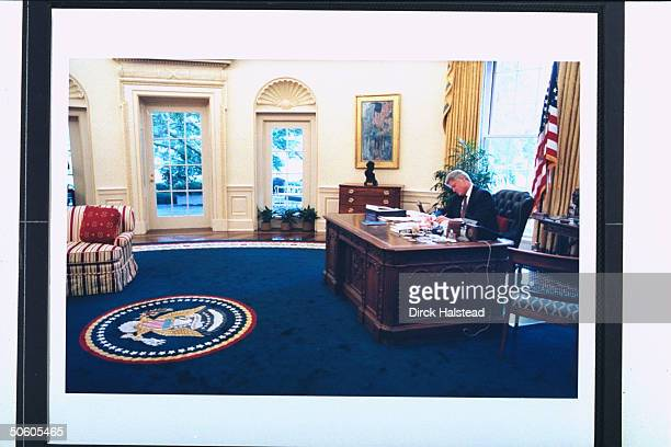 Pres Bill Clinton on phone calling congressmen lobbying for crime bill health care reform working at his desk in panorama of WH Oval Office w its...