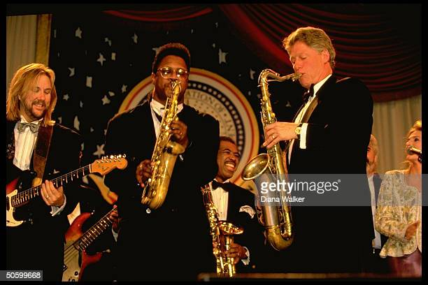Pres Bill Clinton playing saxophone jamming w musicians onstage at DC Armory Ball during inaugural wk festivities