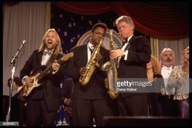 Pres Bill Clinton playing saxophone jamming w musicians onstage at DC Armory Ball during inaugural wk fete