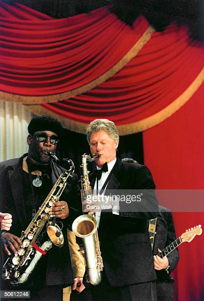 Pres Bill Clinton playing saxophone w musician Clarence Clemons during inaugural celebration at District of Columbia Armory Ball