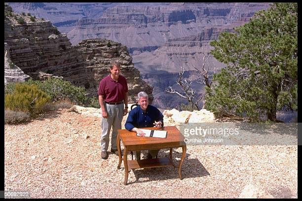 Pres Bill Clinton poised w pen VP Al Gore looking on during signing of proclamation establishing Utah's Grand Escalante National Monument in ceremony...