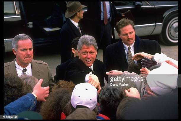 Pres Bill Clinton pressing flesh greeting supporters in street jaunt getting jump start on his reelection campaign somber secret servicemen in escort