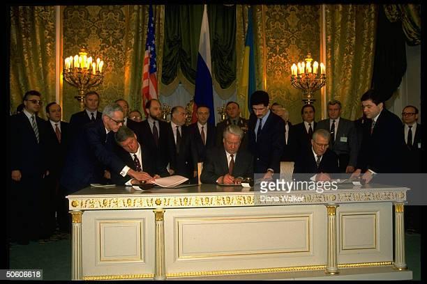 US Pres Bill Clinton Russian Pres Yeltsin Pres Leonid Kravchuk of Ukraine signing nuclear disarmament agreement during Kremlin summit mtg