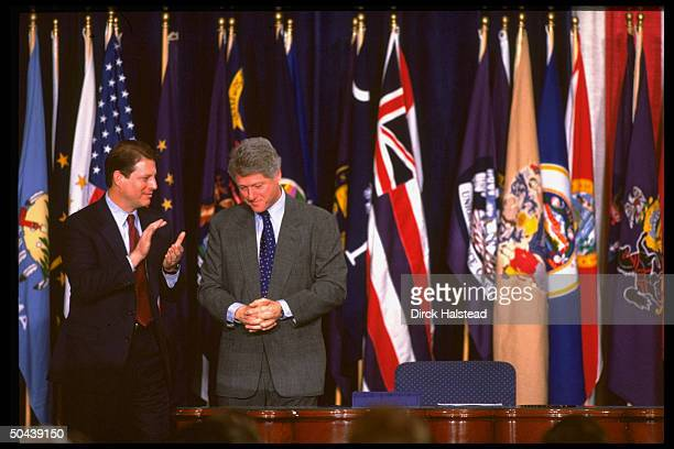 Pres Bill Clinton w applauding VP Al Gore poised by multinatl flag display during signing of NAFTA trade agreement