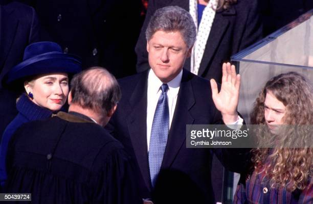 Pres Bill Clinton wife Hillary Rodham Clinton daughter Chelsea looking on being sworn in to office by Chief Justice Rehnquist