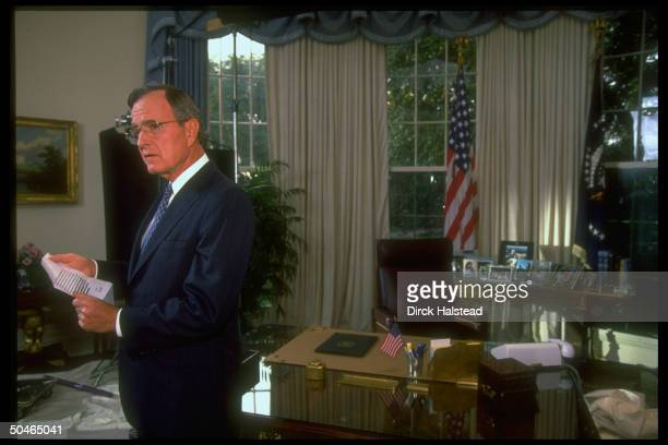 Pres Bush poised in WH Oval Office holding memo