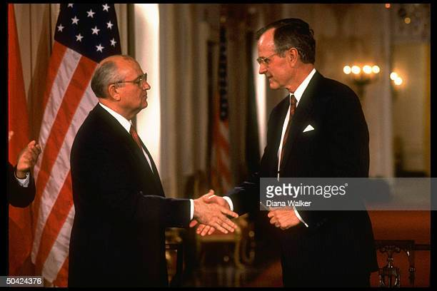 Pres Bush shaking hands w Soviet Pres Gorbachev in flagsadorned WH E Rm during summit agreements signing ceremony