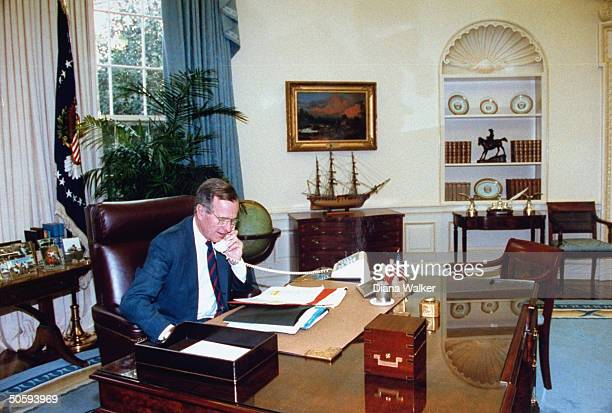 Pres Bush sitting at his WH Oval Office desk chatting on phone pausing fr perusing memotype documents