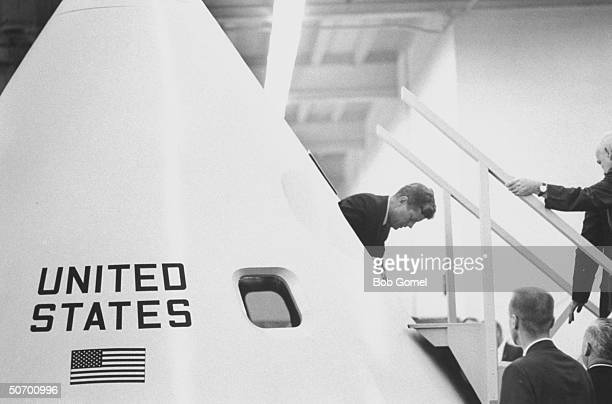 Pres John Kennedy emerging fr inside a model of the Apollo space capsule during his tour of the Manned Space Center