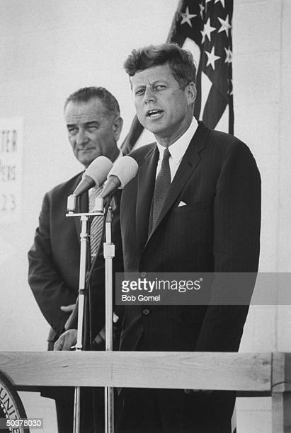 Pres John Kennedy speaking fr podium w VP Lyndon Johnson looking on upon his arrival for his tour of the Manned Space Center