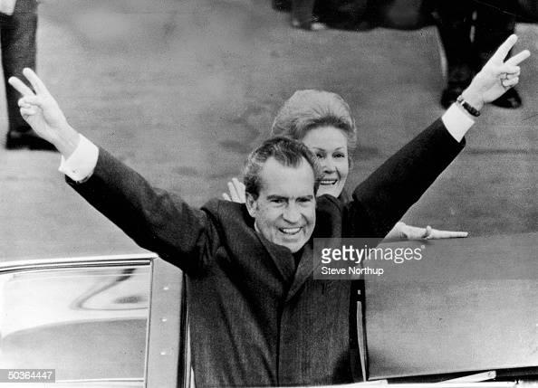 Pres Richard Nixon giving his classic double victory salute to the crowd along his inaugural parade route riding in an open car w his wife Pat