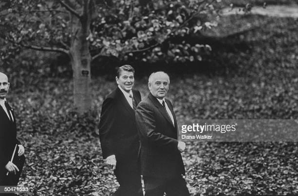 Pres Ronald Reagan walking w Soviet ldr Mikhail Gorbachev outside of WH during successful summit meeting