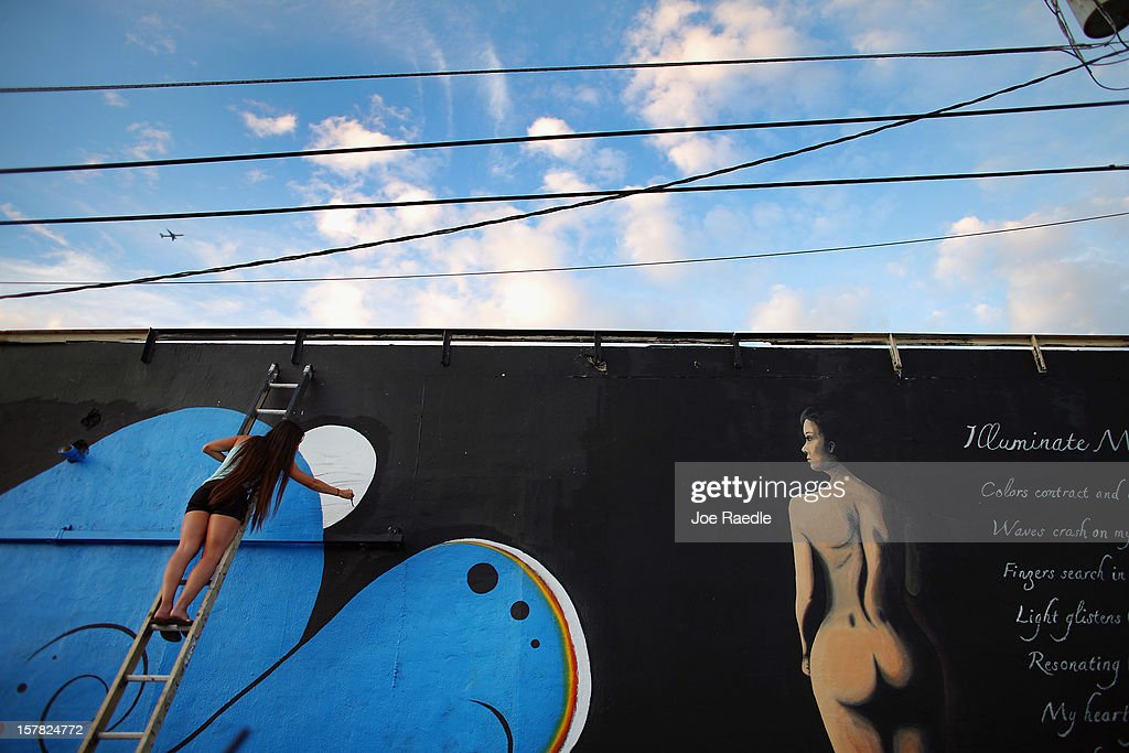 "Presa Hall works on her painting on the wall of a building as she participates in the Wynwood Walls art project on December 6, 2012 in Miami, Florida. The art project along with many other satellite shows around the city coincide with the International art show, ""Art Basel"", which runs until the 9th of December."