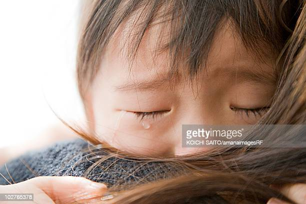 Preschool age girl crying in her mother's arms