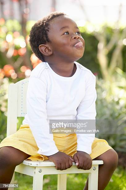 Pre-school boy on a chair sticking out his tongue. Cape Town, Western Cape Province, South Africa