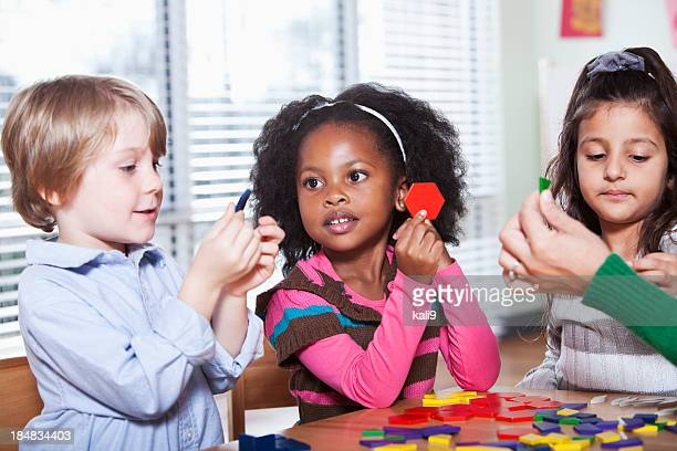 Preschool children in classroom using colorful shapes