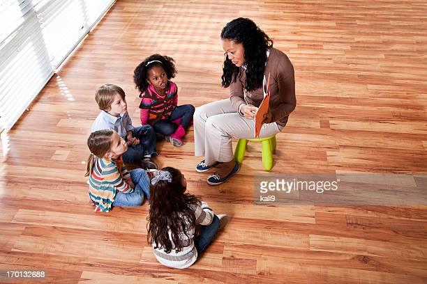 Preschool children reading with teacher in classroom