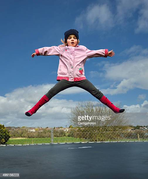 Preschool girl (2-3) jumping on trampoline