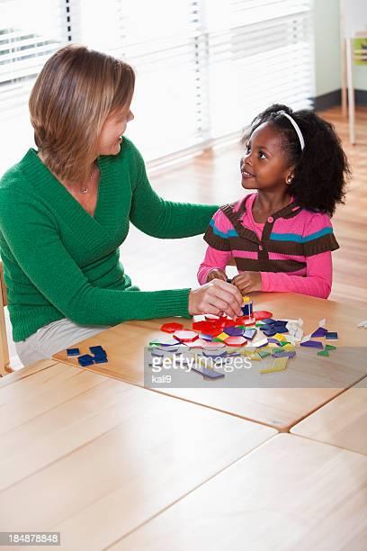 Preschool girl listening to teacher in classroom